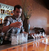 Bar manager John Codd stirring three drinks at once - LOU BUSTAMANTE