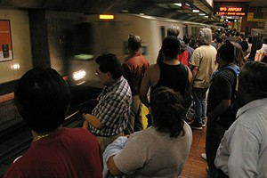 BART commuters looking depressed as they stand behind the yellow line - FLICKR/JUICYRAI