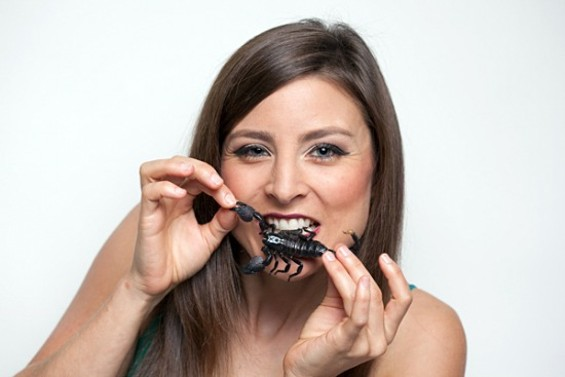 Bay Area entomophagist Daniella Martin tucks into a scorpion - PHOTO BY KIMBERLY SANDIE