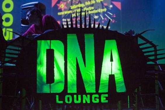 Brian Raffi, the DNA Lounge's original owner, DJing above the venue's original sign.