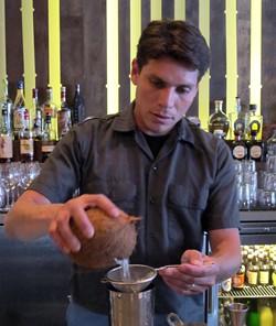 Carlos Yturria cracking a coconut - LOU BUSTAMANTE