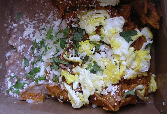 Chilaquiles with refried beans ($6.75) and scrambled egg ($1.50). - JOHN BIRDSALL