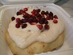 Cinnaholic's Old Skool roll, topped with pomegranate seeds. - TAMARA PALMER