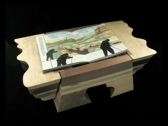 Cloughley's book, Red Rock, Black Sun, is contained in a wooden sculpture. - WILL CLOUGHLEY