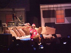 Curren$y rests his broken ankle on stage.