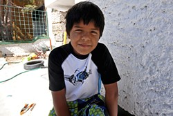 LUIS AGUILAR - Eight-year-old Esteban, pictured here standing outside his family's house, first saw dead bodies two years ago, in a car four blocks from home.