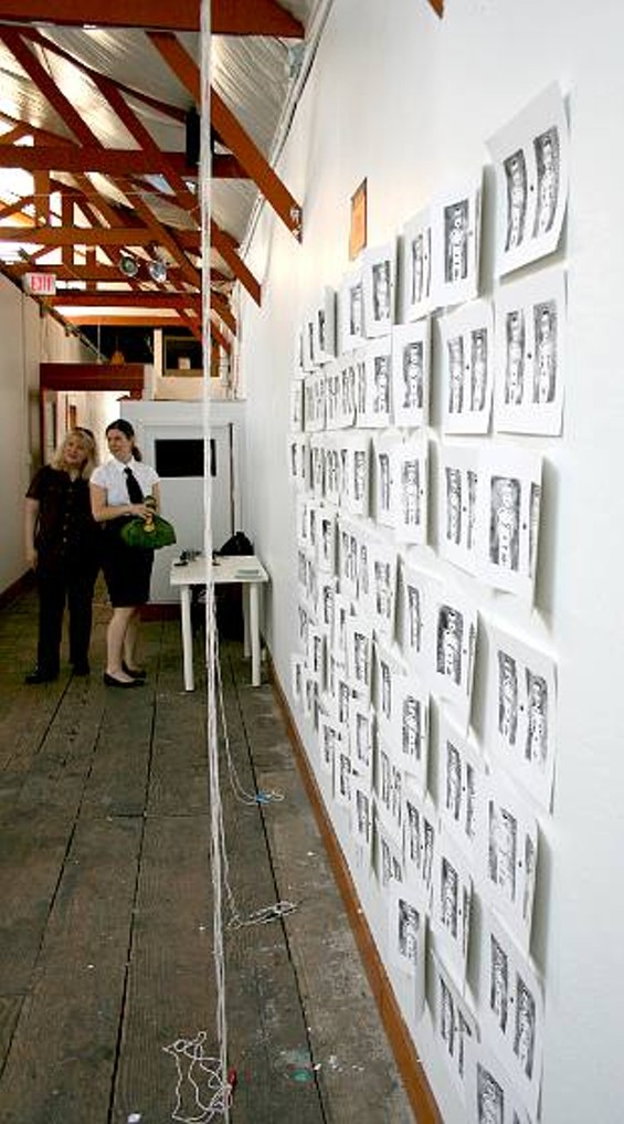 Erin Gallup's mother, left, flew in for the opening. The wall to the right holds copies of the same wood-block print of a naked man and woman.