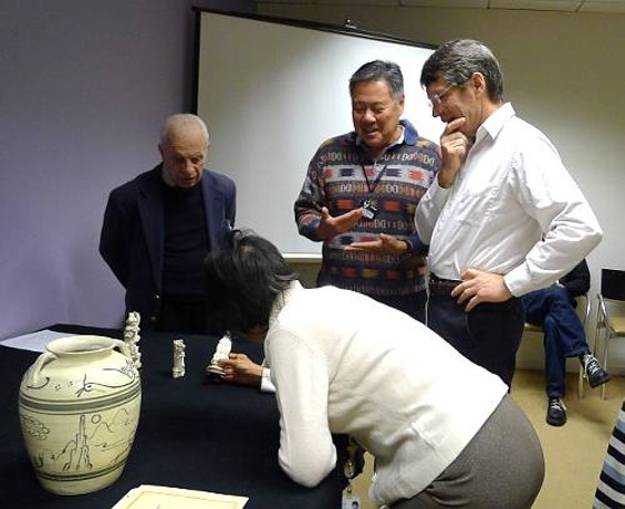 Fred Sheng (center) pleads his case to senior curator Michael Knight as associate curator He Li makes a closer inspection.
