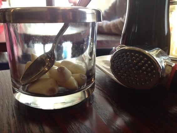 Garlic cloves and a garlic press are table helpers at Waraku. - TAMARA PALMER