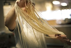 LARA HATA - In the kitchen, a master stretches the noodles into shape.