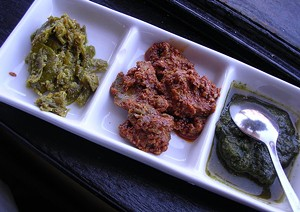 Indian pickles, and at right, house-made green chutney. - JOHN BIRDSALL