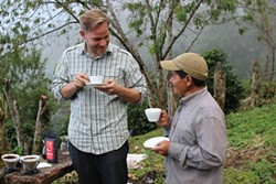KEVIN BOHLIN - Kevin Bohlin (right) drinks coffee made from beans produced in Honduras by his friend and farmer Sebastian Benitez.