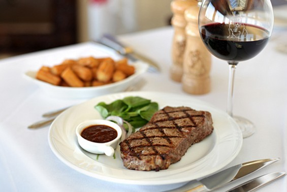 Leatherneck Steakhouse's New York strip and house-made Tater Tots. - LARA HATA