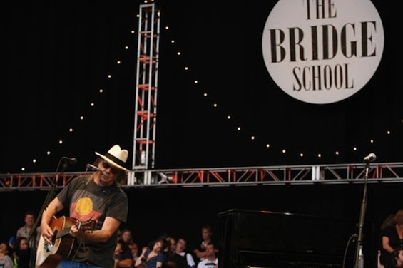 Neil Young performing at Bridge School