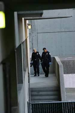 MIKE KOOZMIN - Officials on a walkway near the base of the stairwell Lynne Spalding was found in. The unlocked exit door Spalding could have walked out of is on their right.