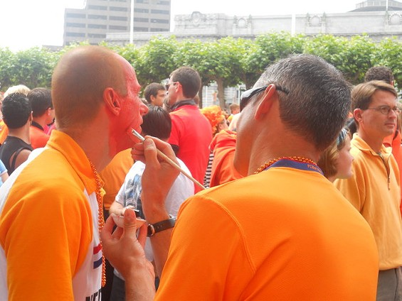 On goes the warpaint -- and another Dutch fan resembles an Oompa-Loompa. Incidentally, the man with the paintbrush was splitting his loyalties: He wore a Barcelona jersey in Dutch orange. - JOE ESKENAZI