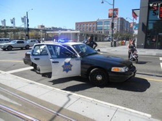 Police lean in to speak with one of the suspects pulled off a T-Third train today after a passenger spotted a fellow rider with a gun - JOE ESKENAZI