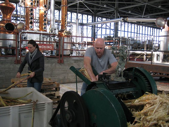 St. George Spirits' Lance Winters, crushing sugarcane at the Alameda distillery. - LOU BUSTAMANTE