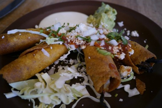 Taquitos de calabaza -- filled with butternut squash and topped with guacamole, salsa, crema, and queso fresco