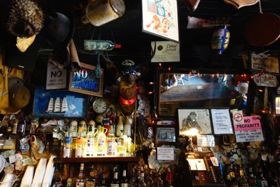 The bar at Heinold's First and Last Chance Saloon, where most items on the wall are over a century old. - FERRON SALNIKER
