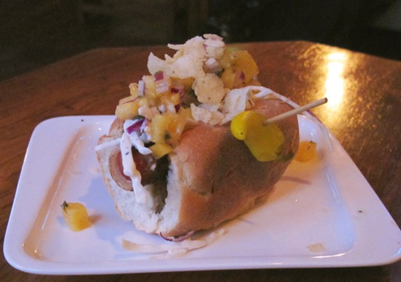 The Colombian hot dog topped with pineapple salsa and crumbled potato chips - LOU BUSTAMANTE