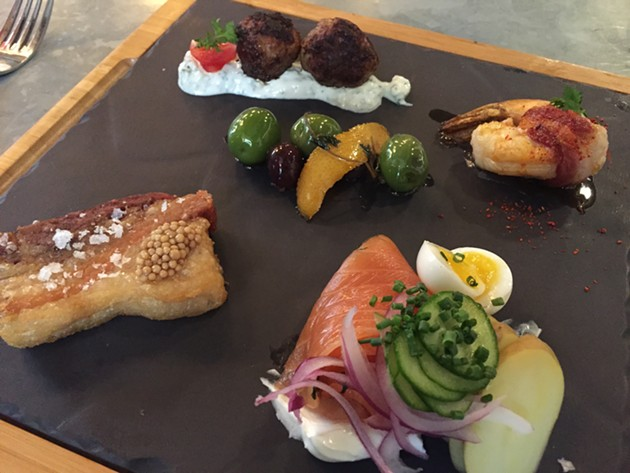 Bar snacks (clockwise from left): crispy pork belly, lamb meatballs, marinated olives, chorizo shrimp, and dill gravlax. - PETER LAWRENCE KANE
