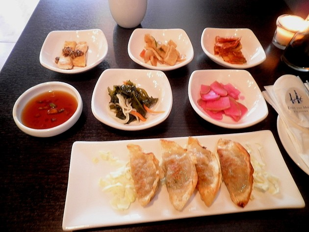 Dumplings and banchan. - ERIC S. BURKETT