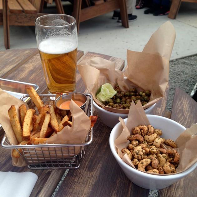 Togarashi fries with Sriracha mayo, Hella Hellie's lager, crispy green chickpeas, chimichuri cashews. - A.K. CARROLL