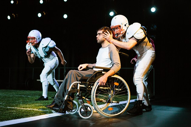 Mike, in a wheelchair, (Jason Stojanovski) and his younger self (Thomas Gorrebeeck*) view playbacks of the defining play that changed his life. - JESSICA PALOPOLI