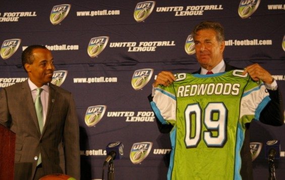 UFL Commissioner Michael Huyghue smiles while California Redwoods owner Paul Pelosi shows off what is either a large Jolly Rancher candy or his team's road uniform - JOE ESKENAZI