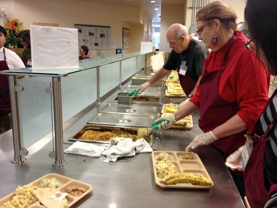 Volunteers load up plates of food for St. Anthony's visitors. - ANNA ROTH