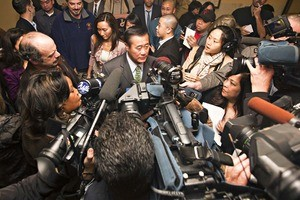 Yee surrounded by a scrum of reporters.