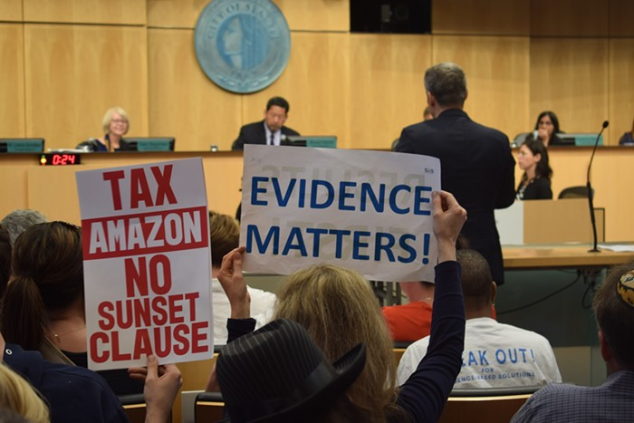 Dueling signs at City Hall over the head tax