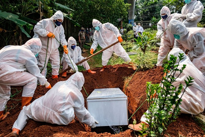 Health workers in Jakarta, Indonesia bury someone suspected of dying of COVID-19.