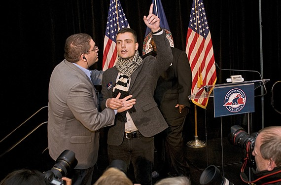 A CASA in Action member is escorted from the stage after disrupting the Republican Party of Virginia election night party. - ASH DANIEL