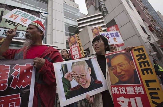 A group of pro-Democracy protesters hold signs picturing Liu Xia (left) and Liu Xiaobo outside of the Chinese liaison office in Hong Kong on Dec. 25, 2012. They called for the release of Liu Xiaobo, who was sentenced to 11 years of imprisonment on Christmas Day in 2009.