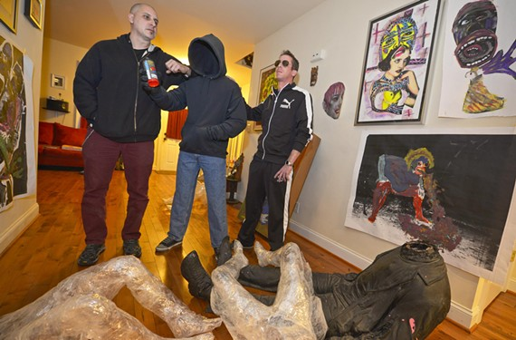 Acclaimed street artist Mark Jenkins, an Alexandria native, poses with one of his tape sculptures molded in the image of his college friend, graffiti artist Chad Niemi, at right.