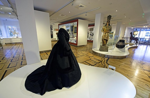 "An 1864 mourning dress and  Old Chief Smokum, a cigar store figure from 1885, anchor the exhibit ""This Is Richmond, Virginia"" at the Valentine. Windows and a wooden floor painted by artist Nancy Beck create a sense of openness."