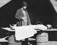An embalming surgeon works on a soldier's body during the Civil War in an unknown battle. After the war, embalming became widespread.