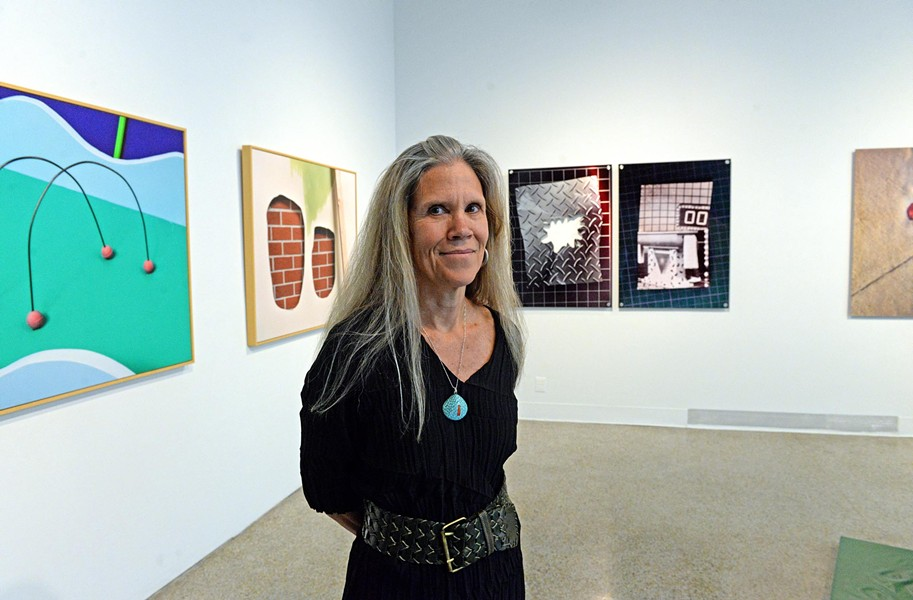 Ashley Kistler, the Anderson Gallery's sixth and final director since it opened in 1970, stands amid the graduate thesis exhibition that closes May 17. She and gallery staff are preparing a book that will examine the institution's more than 45-year history. - SCOTT ELMQUIST