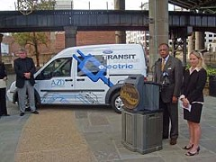 Azure Dynamics Director of Sales Jeff Hyatt stands next to the Transit Connect Electric as Mayor Dwight Jones, with city Sustainability Manager Alicia Zatcoff, prepares to speak.