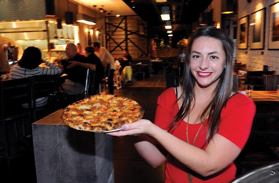 Bartender Lauren Spain serves the spicy sausage and black pepper honey pizza at Tazza Kitchen, where rustic, wood-fired dishes highlight the menu.