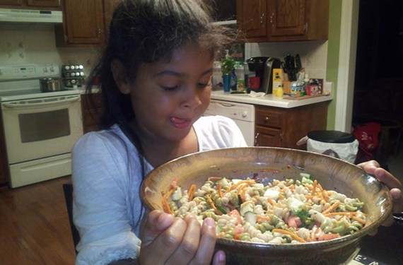 Bella Jenkins helps prepare a meal in a bowl made by Richmond artist Carren Clarke-McAdoo. - PHOTO COURTESY SHARON RUSSELL