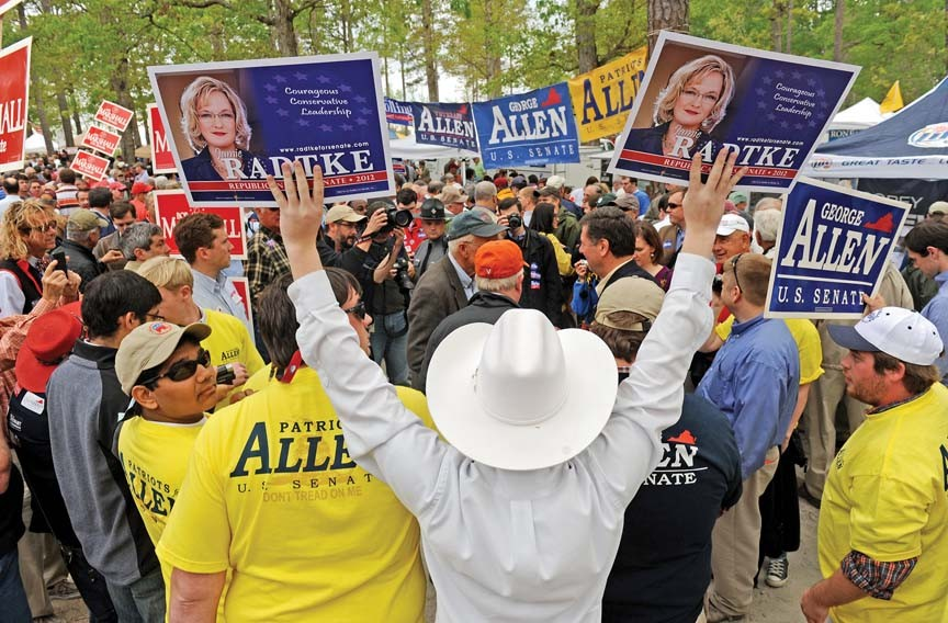Blocked by a row of handlers for former Gov. George Allen, one of Jamie Radtke's supporters holds the candidate's signs high at the Shad Planking. - SCOTT ELMQUIST