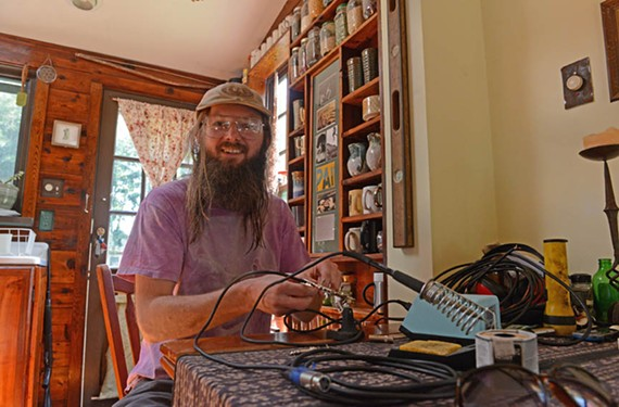 Brent Delventhal of Warren Hixson messes around with soldering his own guitar cables inside his Fulton home.
