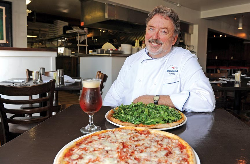 Chef and owner Jimmy Sneed shows the Edwards & Sons pizza with smoked sausage, Surry bacon, ham and mozzarella; and the Surryano pizza with ham, arugula and Parmesan, complemented by a Devil's Backbone Vienna lager at Carytown's BlowToad. - SCOTT ELMQUIST