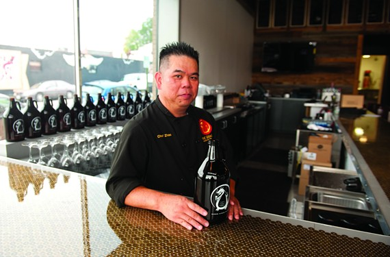 Chef Jin Zhao is surrounded by signature beer growlers at Fat Dragon, which will emphasize local beer culture to go with his Cantonese cooking. The bar is embedded with lucky coins from China. - SCOTT ELMQUIST