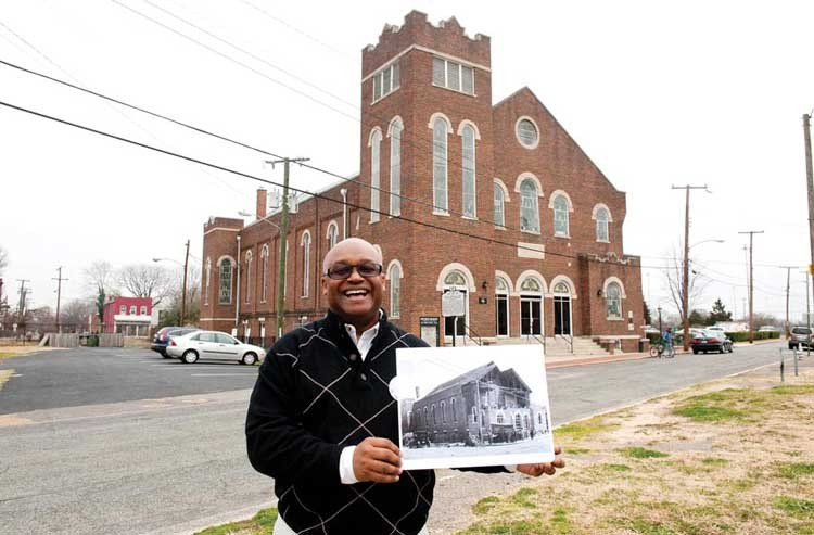 Church historian Benjamin Ross holds a photograph of the 1926 renovation of Sixth Mount Zion. Thirty-one years later, Interstate 95 came roaring past the historic building. - SCOTT ELMQUIST