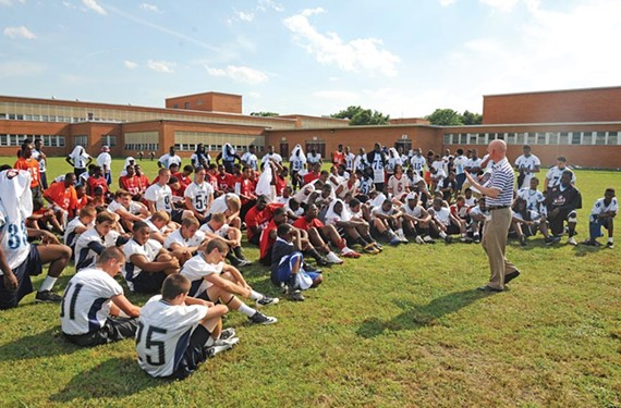 City Councilman Chris Hilbert talks to players after practice at John Marshall High School on Thursday. - SCOTT ELMQUIST