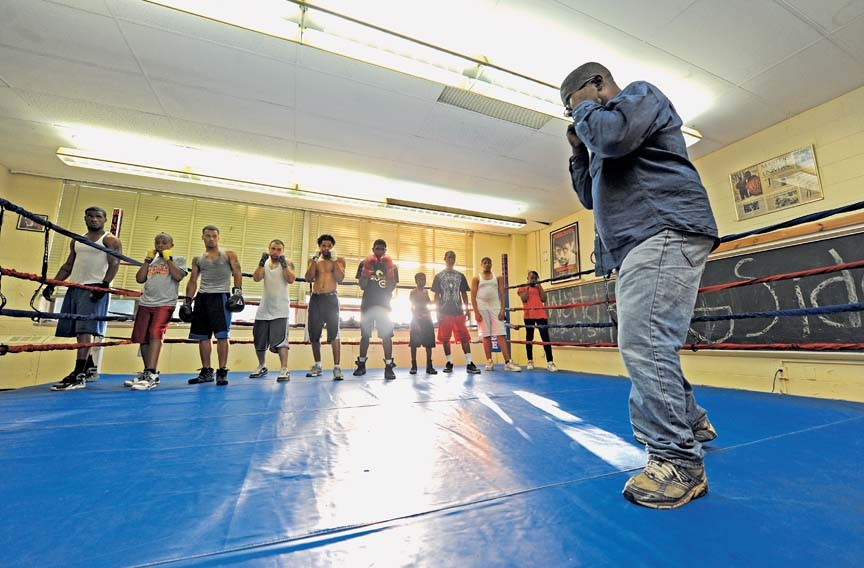 "Coach Royster stresses the fundamentals to his young boxers. ""The only time you should see the palm of your hand is when you throw an uppercut,"" he tells them. - SCOTT ELMQUIST"